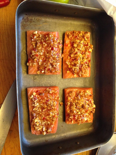 Porsjonsstykker med laks smurt tykt med nøtte- og chilisaus.